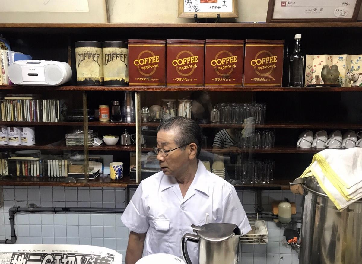 咖啡吧檯裡的牆面一排舊咖啡鐵罐、各式杯子、錄音帶和收音機,一面牆就是一個世代風景。