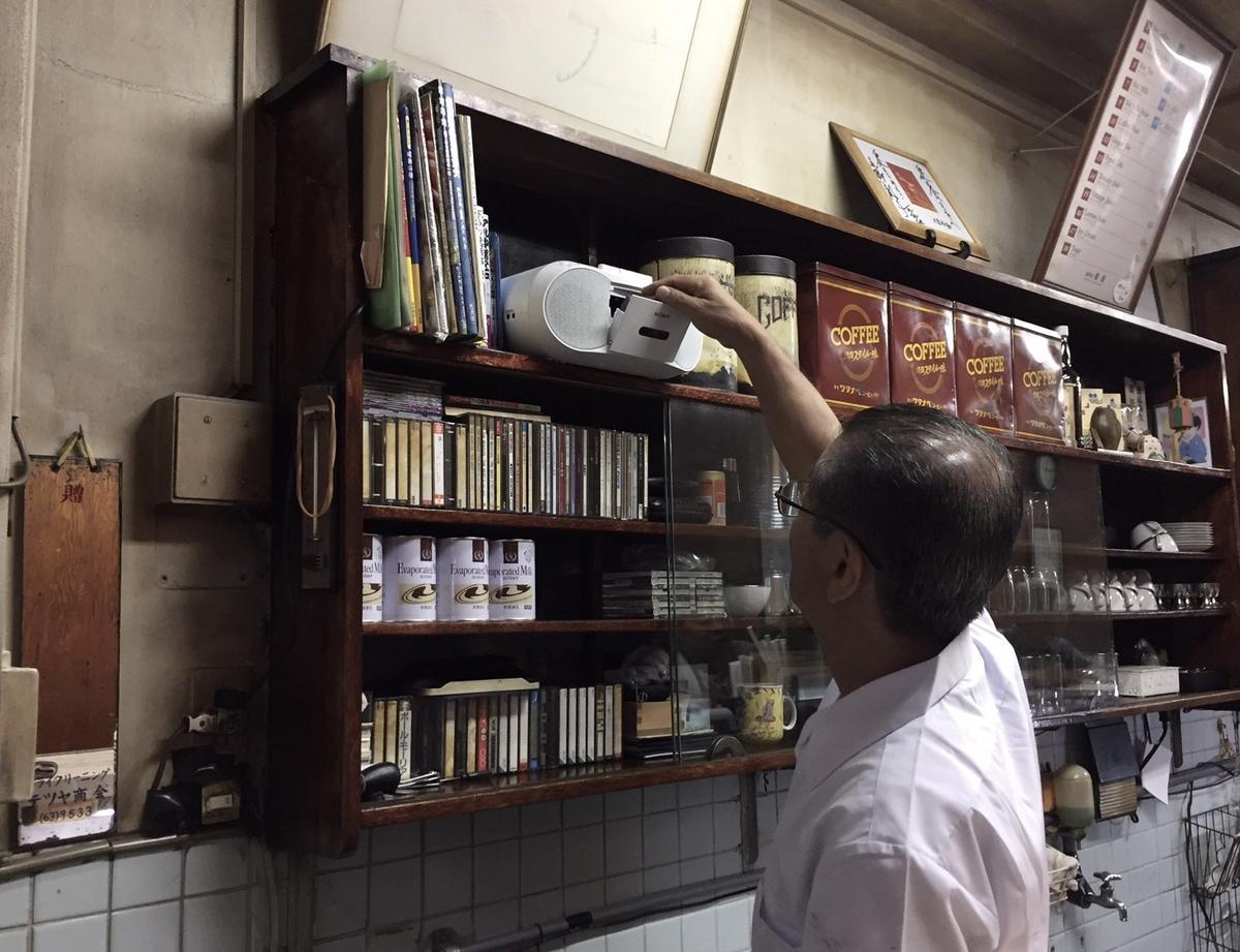 咖啡師工作空檔轉身為錄音帶翻面再播放,錄音機流洩出的是日文老歌旋律。