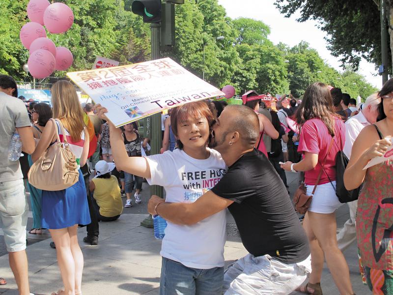 十多年來,丘愛芝參加國際陰陽人運動與同志運動,造訪數十個國家,見過上百位陰陽人,他總是隨身攜帶著「擁抱陰陽人」的標語牌子。(丘愛芝提供)
