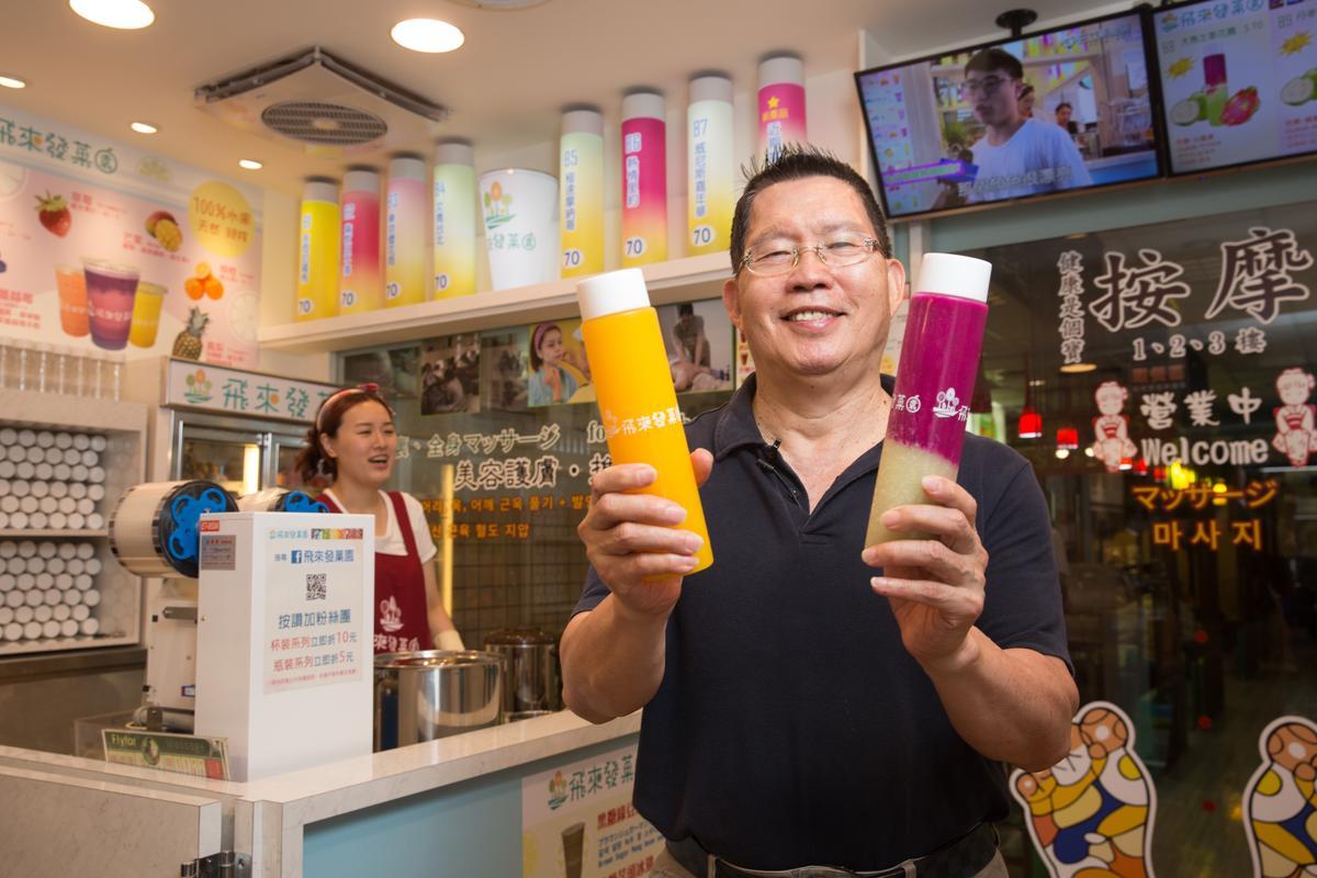 看好現打的新鮮果汁在食安風暴後有市場,黃有忠(右)在店內一角做起果汁生意。
