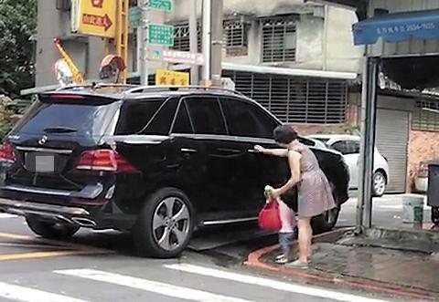 26日李朝永的車子又開到獅奶奶家附近,只見她牽著一個約3、4歲孫輩小女孩上車,因為穿洋裝,上車時獅奶奶還露了一腿,微露性感風情。(讀者提供)