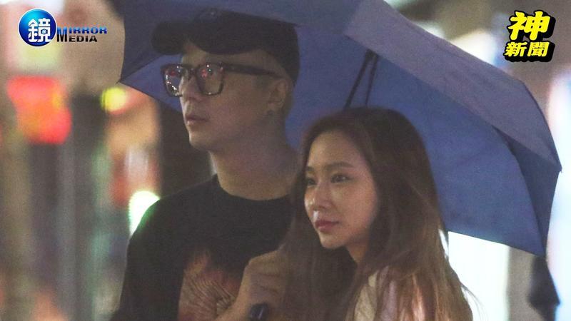 廖人帥和D奶妹在街頭共撐一把傘。