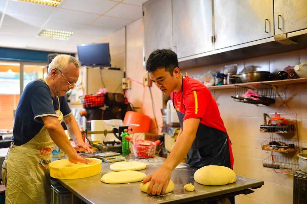 老餅店的第二代老闆周德勝(左)和兒子周揚志(右),每天一起在老餅店分工做餅。