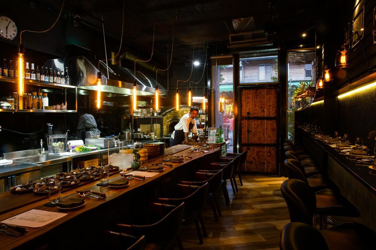 原木、鐵件與鎢絲燈泡架構的粗獷工業風空間,呼應Akame柴燒料理的豪邁。