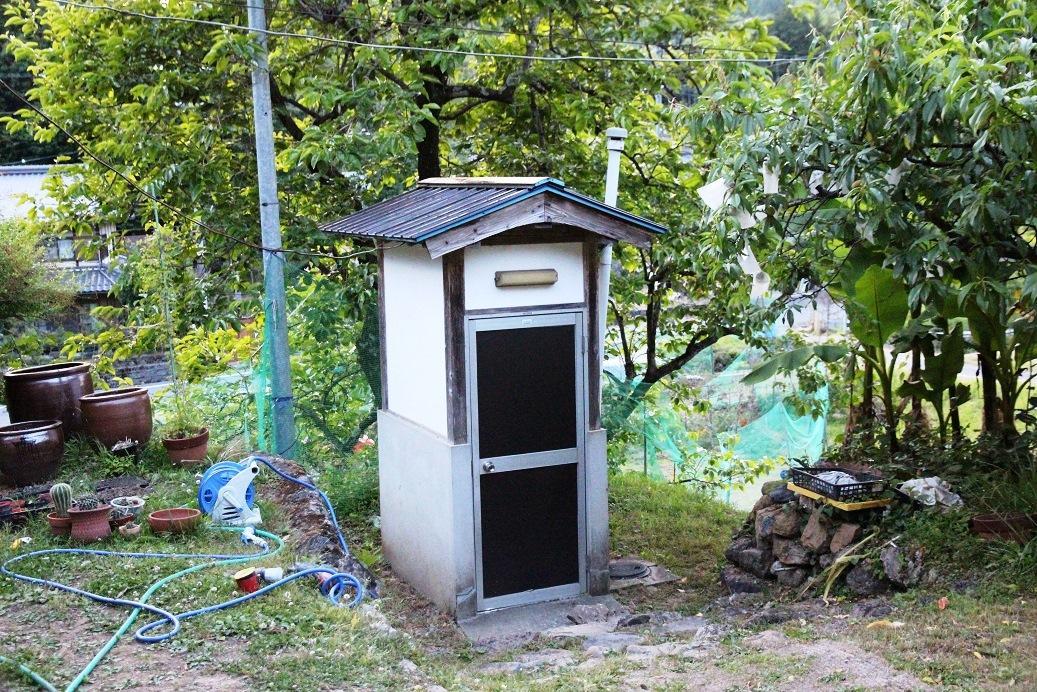 戶外的廁所,簡單的隔間,裡頭是一個坑。