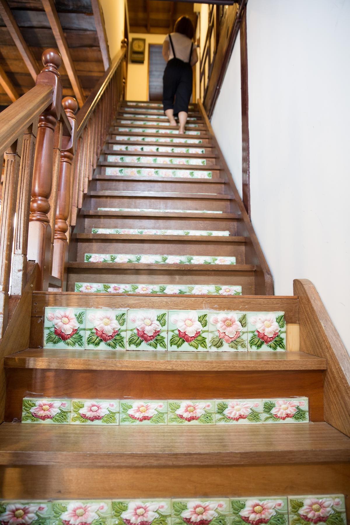 新屋主以老工法打造木樓梯,花磚朵朵開滿階梯。
