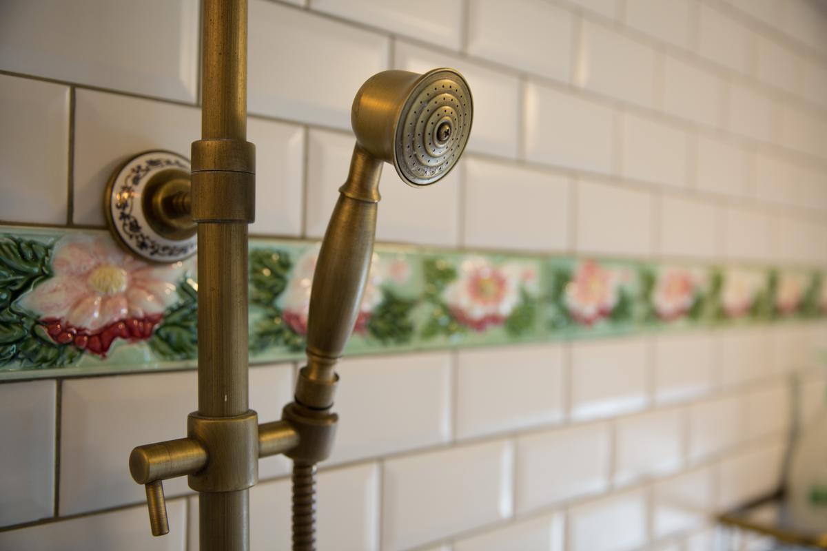 浴室牆面貼上花磚腰帶。