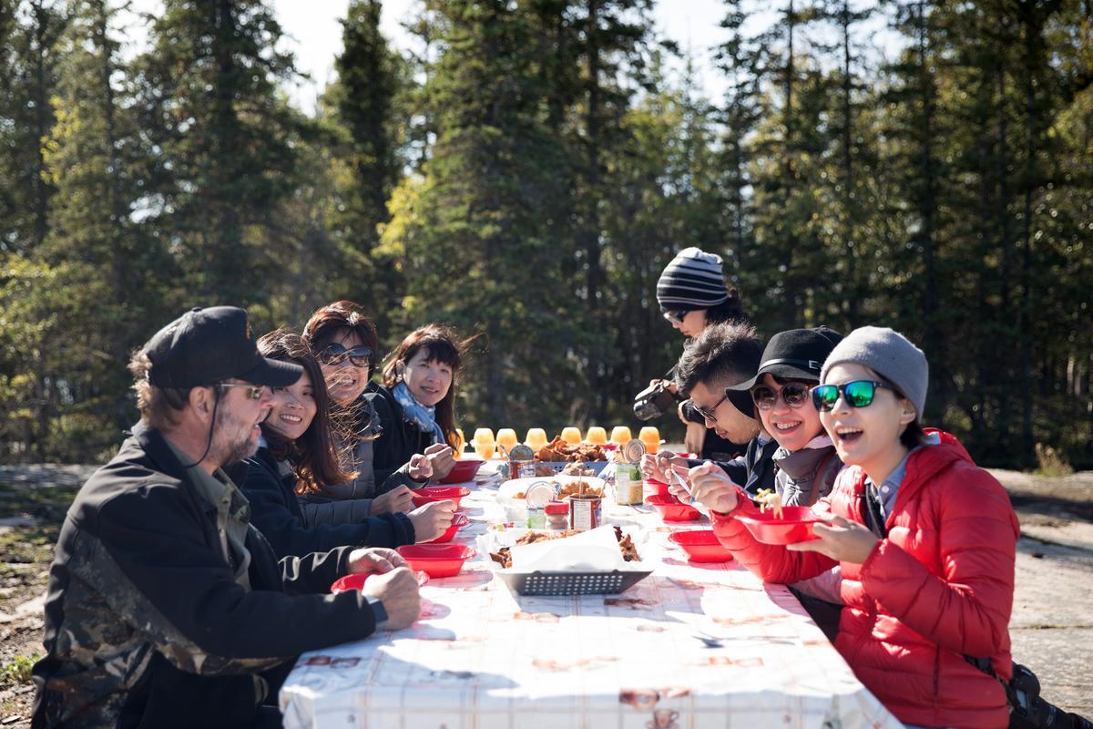 一群人在風和日麗的湖畔,品嘗鮮美的湖魚、現做的麵包與紅莓果醬,好不愜意。