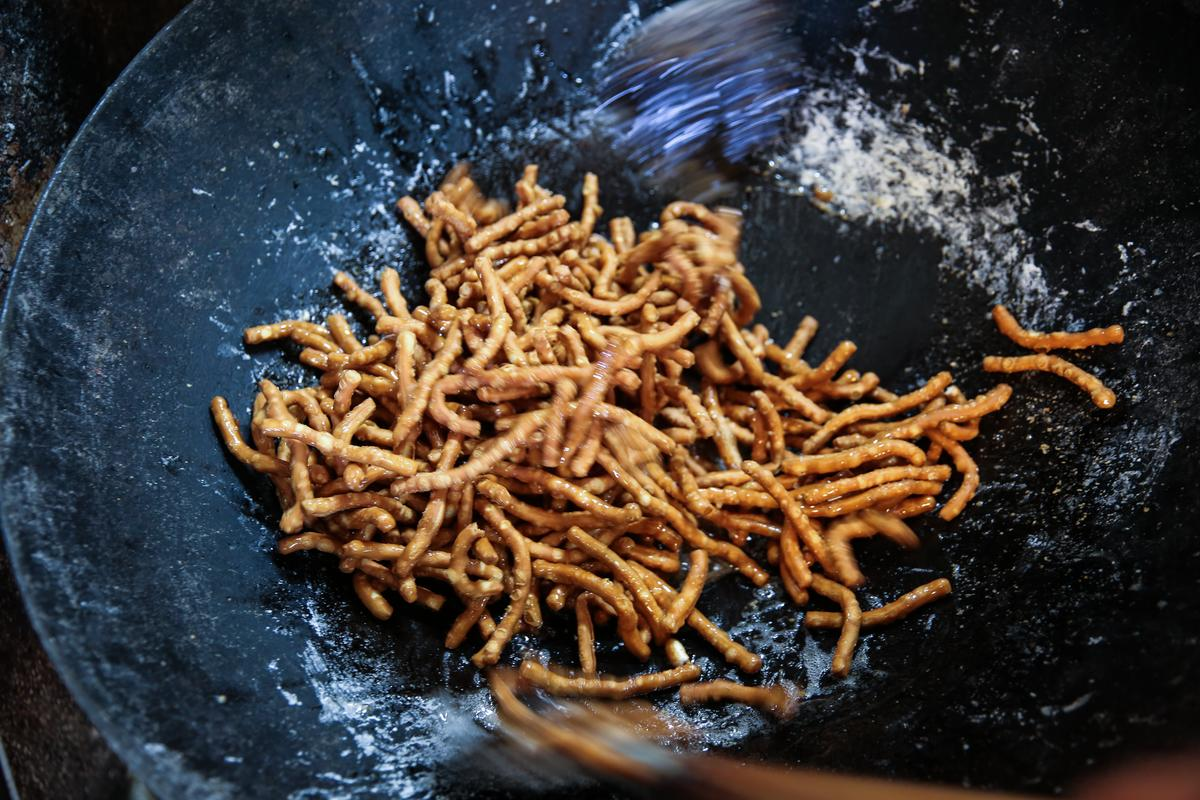正在鍋裡與白色糖漿翻炒的「寸棗」,鍋邊熱氣裡飄散著糖香。