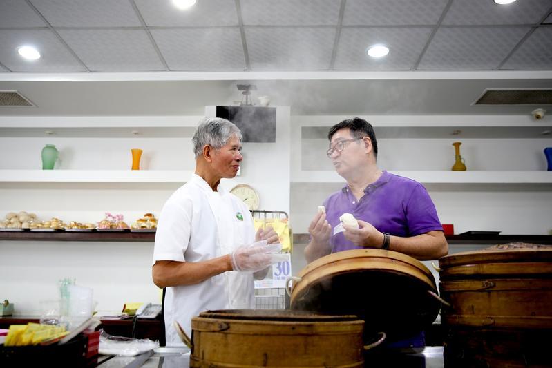 文藝大叔王浩一(右)帶我們走訪台南私房老餅店,他和「萬川號」老師傅蔡煌明(左)談起店裡百年老包子的身世。