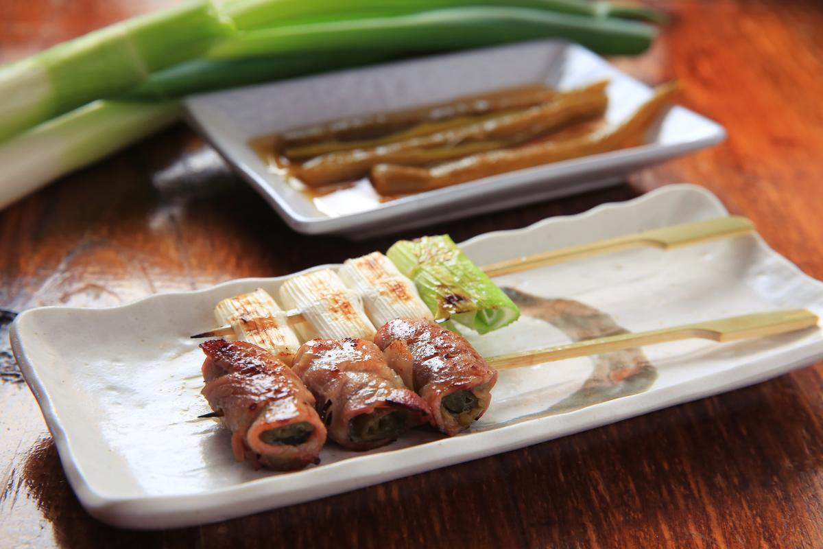 「極黑豬剝皮辣椒卷」(前,70元/串)包的青辣椒有脆度、辛辣味,與豬肉相當對味。「烤日本大蔥」(後,120元/串)嘗起來香甜無蔥辣。