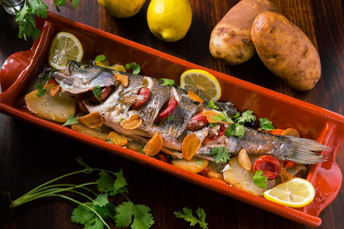 「葡式燒焗鱸魚」是將蘆筍塞在鱸魚裡,表皮劃刀擺進葡式香腸,淋點白酒、檸檬汁後進烤箱,味道略鹹的葡腸會帶出鱸魚的甘美。(時價,約900~1,200元/份,需預訂)