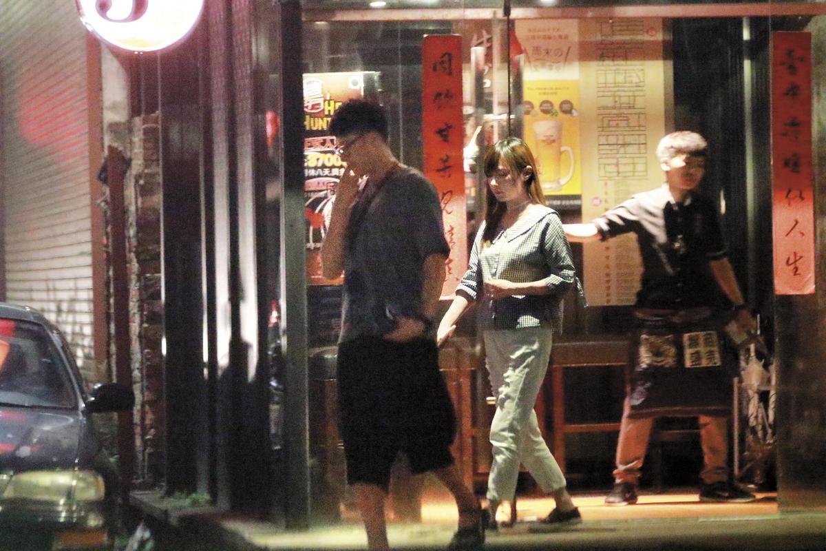 8月13日22:56,用完餐後張睿家步出餐廳,女友低頭跟在後面。