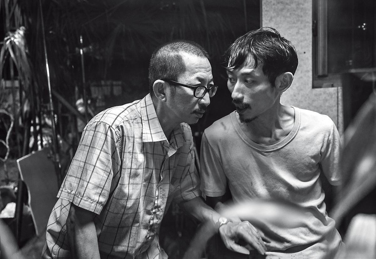 陳竹昇(右)在片中常來找當工廠警衛的莊益增(左),兩人偷看老闆行車記錄器影像,竟意外目擊一件凶殺案。