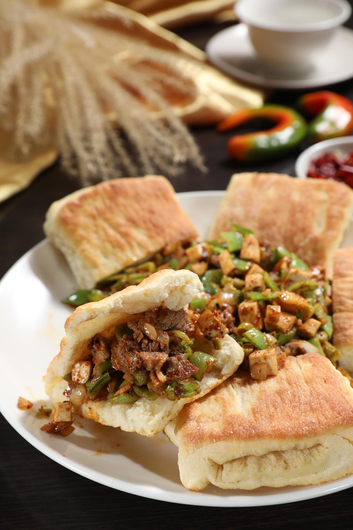 「烙饃」的內餡用甜豆、酸豇豆、豆乾丁等配料炒碎肉,包在酥香饃裡大口咬最過癮。(300元/大份)