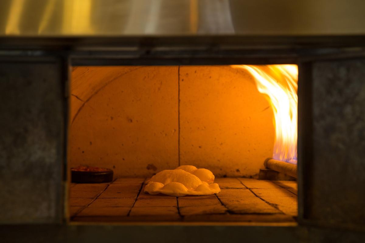 巨大烤窯火力果真非凡,麵餅入窯,三兩下就膨脹出討喜氣泡。