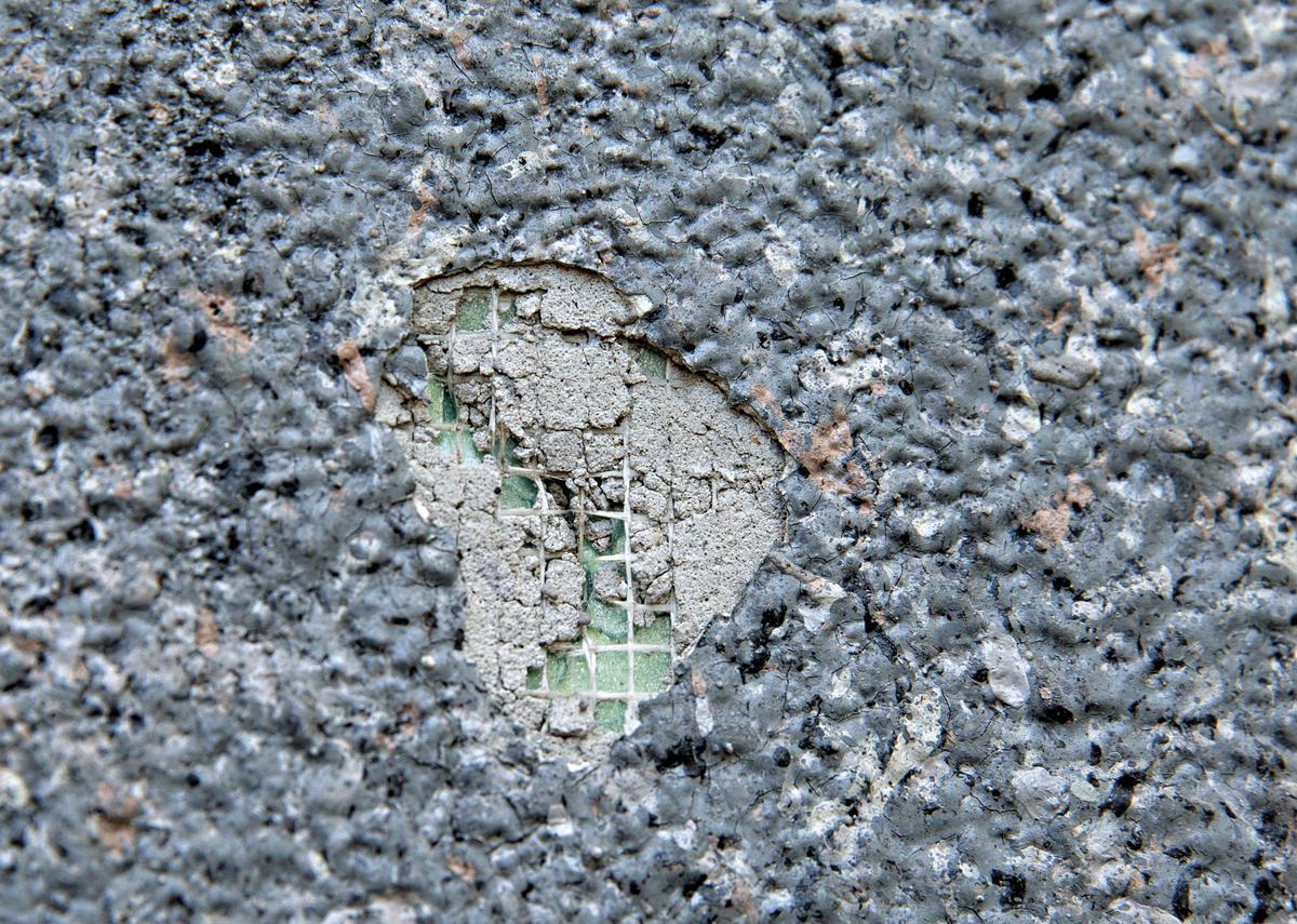 民榮超市大樓西側外牆表層石材塗料剝落嚴重,聚乙烯材質明顯外露。