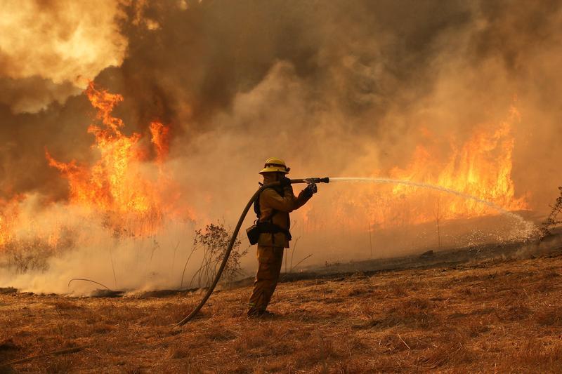 2017年10月11日,美國加州聖塔羅莎一名消防人員在大火中正努力搶救東班尼特谷路的民宅。(東方IC)