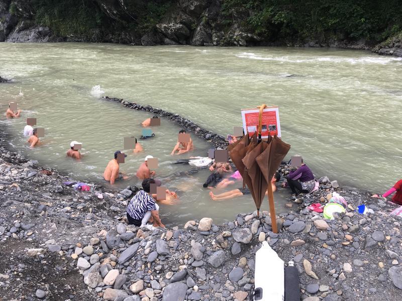 民眾無視禁令進入封閉區,溪邊矗立的告示牌甚至成為民眾的傘架。