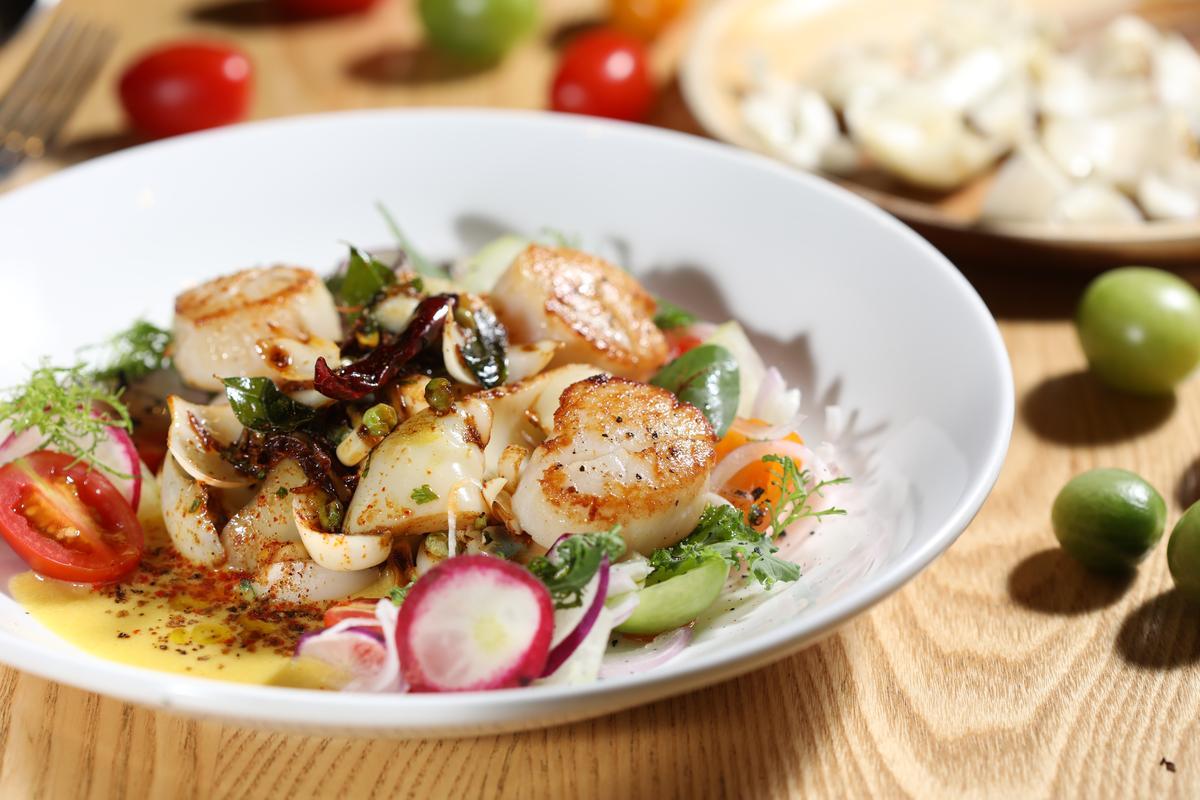 「干貝百合熱沙拉佐甜玉米泥」加進用芥末子、茴香、乾辣椒燴炒的百合花,以及新鮮玉米泥和羅望子醬,讓香煎的干貝吃起來有酸有甜、爽脆開胃。(580元/份)