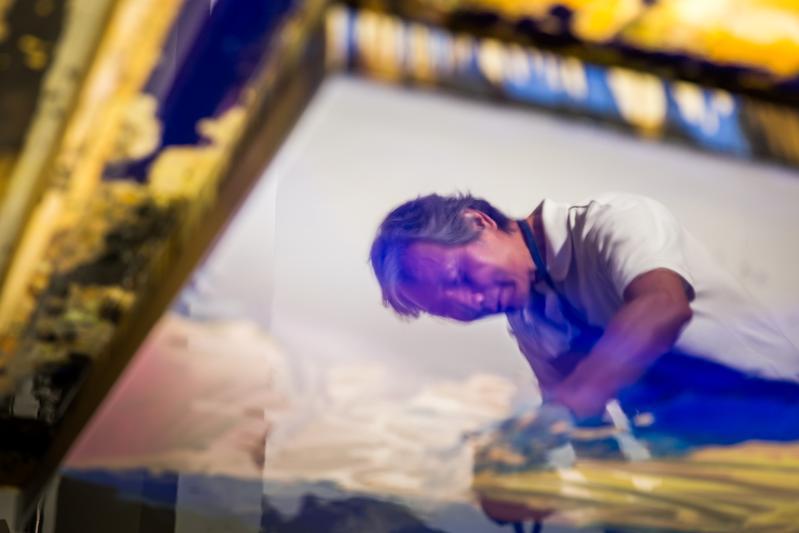 作畫中的蔡文雄,畫板上的油彩出現他的倒影。