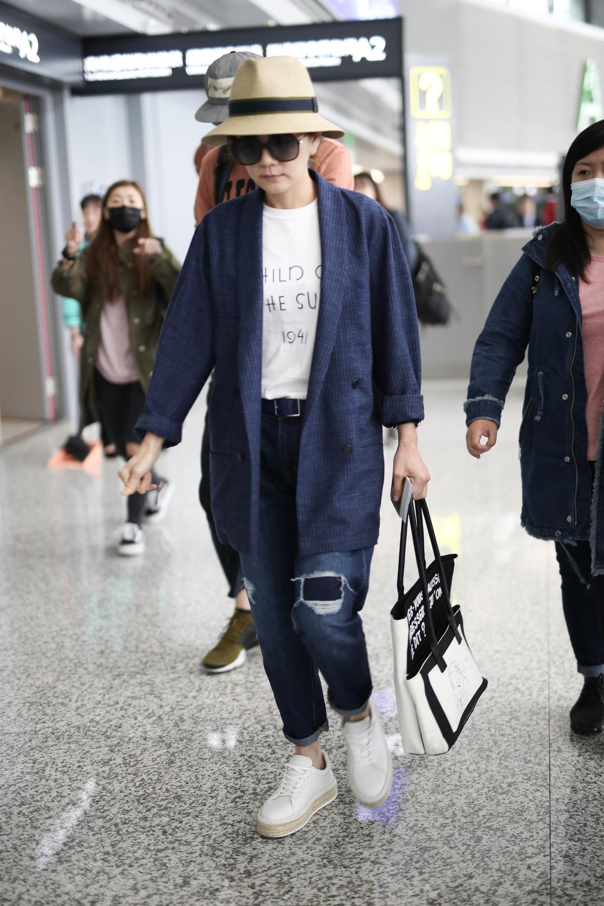 Ella:一向走帥氣路線的Ella,結束上海的節目錄影後抵達機場,她運用簡潔的西裝外套搭配看似兩個,實為一體的法文標語購物袋,品味獨特。(東方IC)