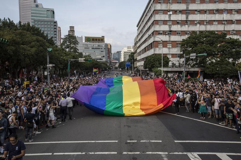 同志遊行開始前,由一大面的彩虹旗領頭往前走,道路兩旁都擠滿參與遊行的民眾。