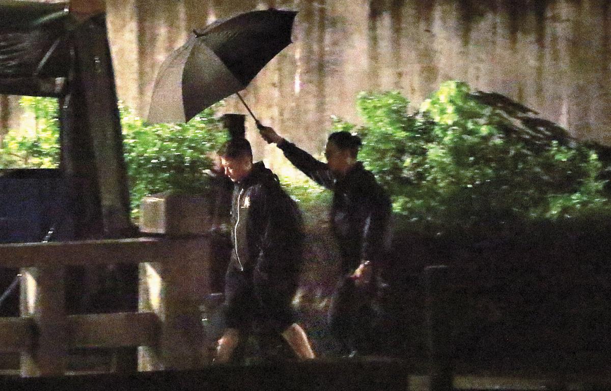 平溪夜裡飄著雨,擔任導演的錢嘉樂(左)有工作人員幫他撐傘,待遇果然不同。