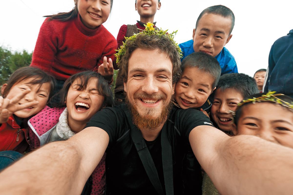 徒步經過甘肅村莊,一群小朋友做花環戴在雷克(中)頭上,這是他徒步中國最美好的回憶。(雷克提供)