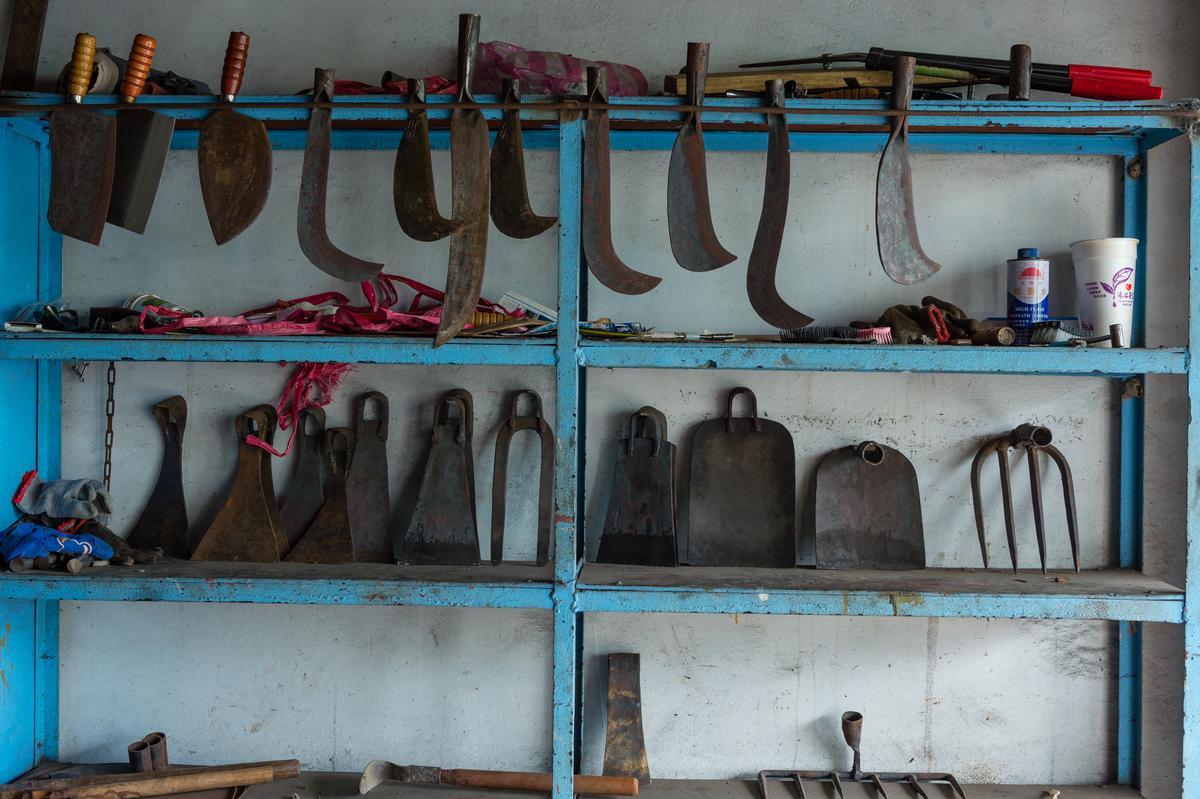 打鐵鋪牆面掛滿各式農具。