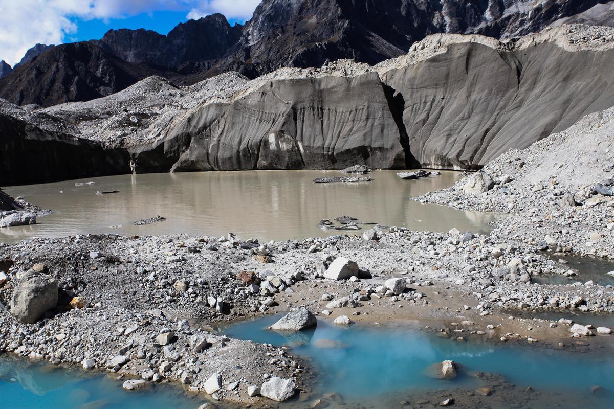 融雪時期,不時有石塊掉入冰川上的小水塘。