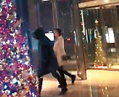 12/9 一身黑衣黑帽包緊緊的洪天明(左),與辣妹到日航飯店開房。(讀者提供)