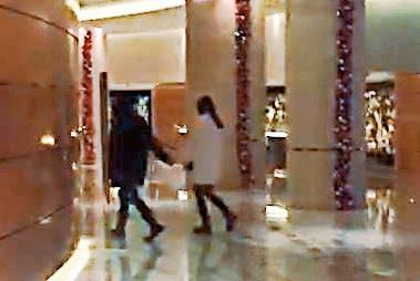 12/9 洪天明(左)與辣妹手牽著手上樓度春宵,看來與一般情侶無異。(讀者提供)
