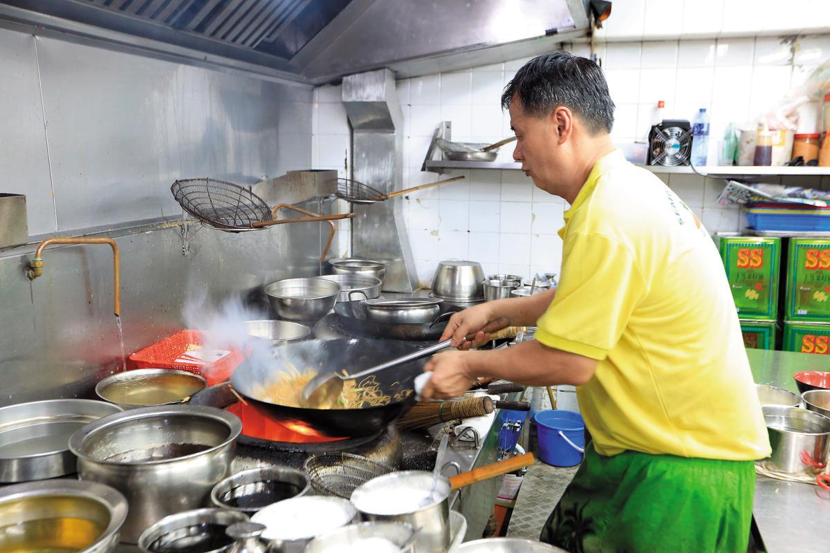 廚師正在大火翻炒麵條,鑊氣十足。