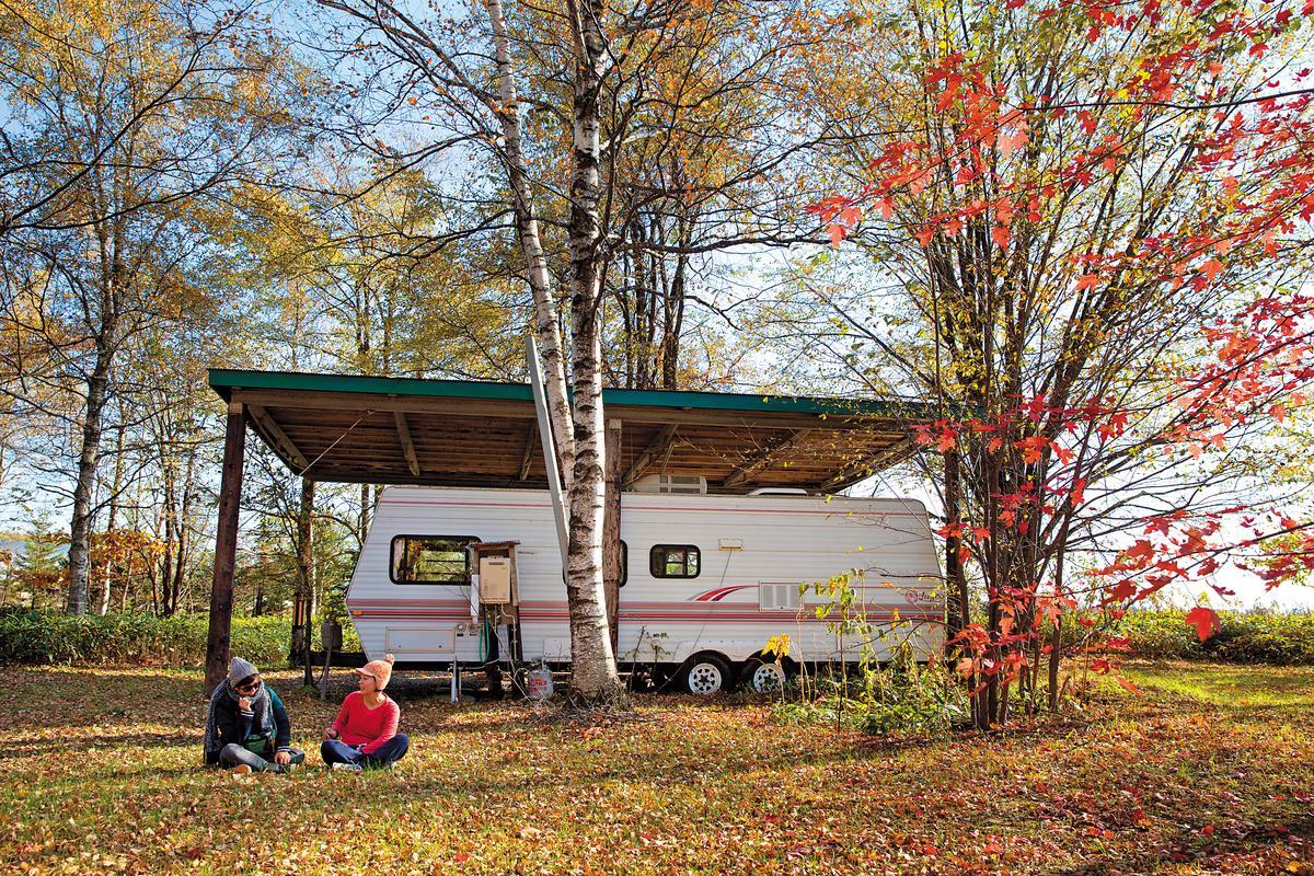院內停著一輛露營車,車旁全是紅葉。