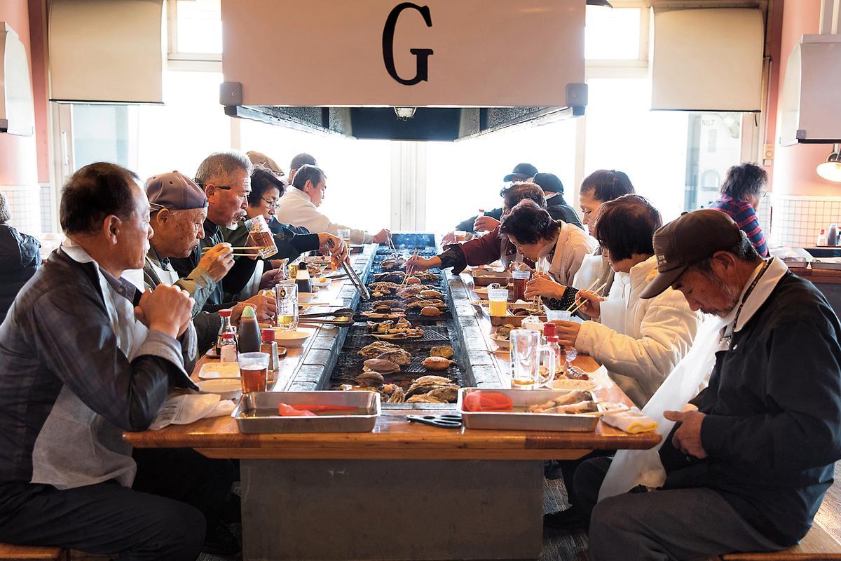 一群人坐在烤爐前面大啖海鮮,豪邁吃法非常過癮。
