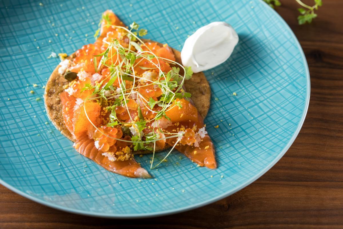 秋柿為「富士鱒鮭沙拉」帶來絕妙明亮的甜味。(2,000元起套餐前菜)