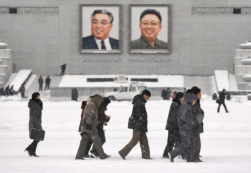2017年12月20日,平壤,北韓民眾走過懸掛金日成父子巨大肖像的金日成廣場。(東方IC)