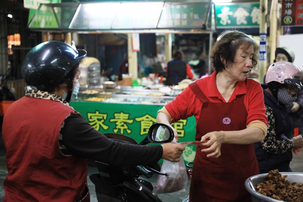 採買的婆媽們會把摩托車騎到攤子旁,一手百元鈔換一袋排骨酥,回家加菜。