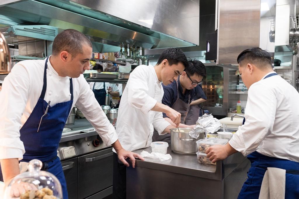 三位主廚在廚房裡互相支援。