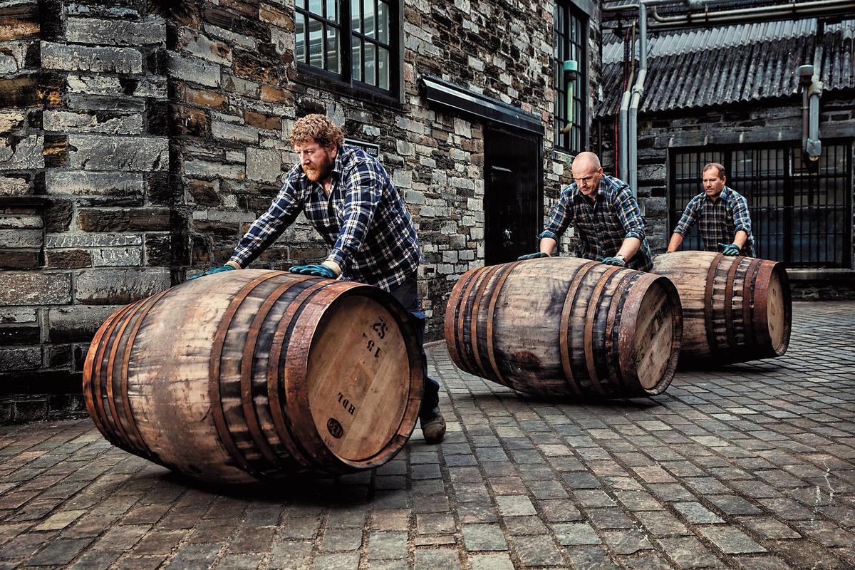 酒廠工人推著酒廠引以為傲的頂級雪莉橡木桶。