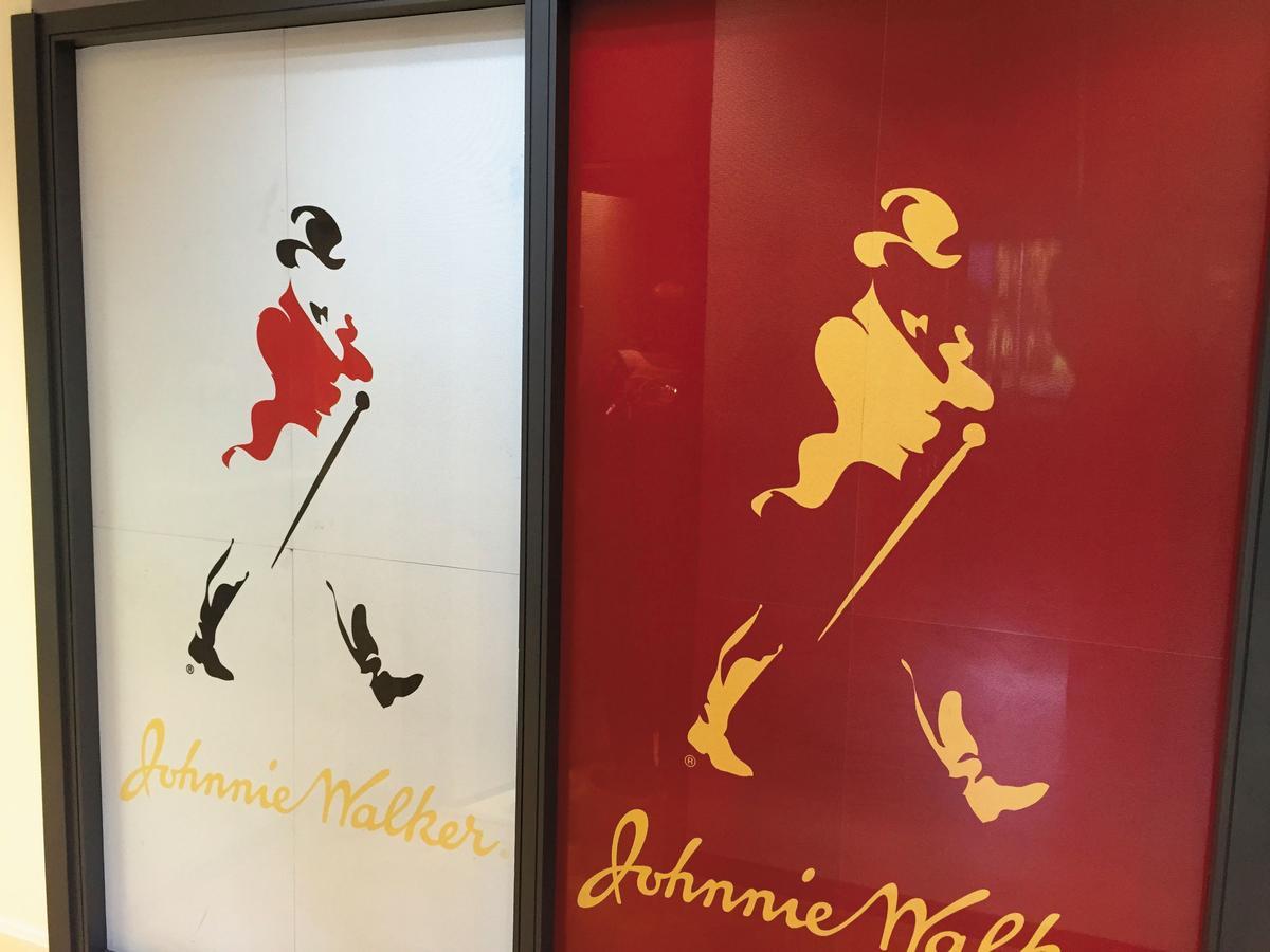 JOHNNIE WALKER的品牌標誌為「邁步向前的紳士」,為插畫家湯姆・布朗1908年設計,隨著時代推演也變化了許多版本。