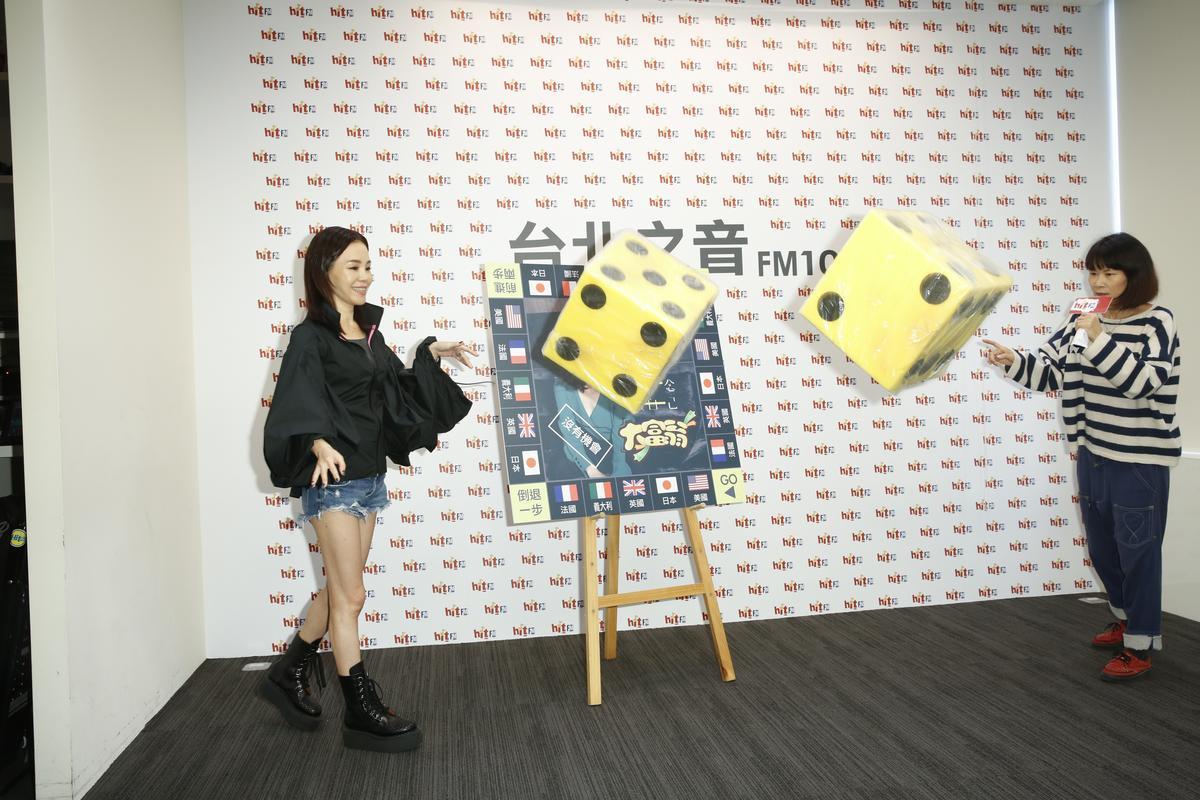 在Hit Fm的活動中,彭佳慧擲骰子來選一個自己想去的地方,彭佳慧很用力,看來真的很想去旅行。
