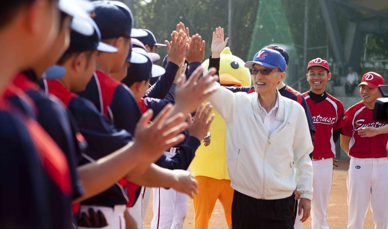永慶房產集團董事長孫慶餘參加集團舉辦球賽,開心與員工擊掌。