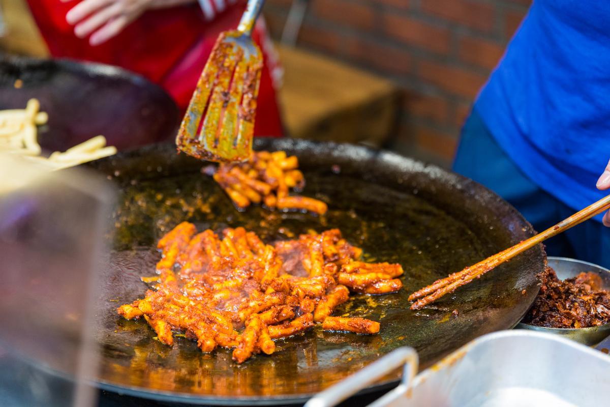 元祖鄭奶奶的年糕會在油鍋先炒,收乾些醬汁,有別於一般年糕濕潤口感。