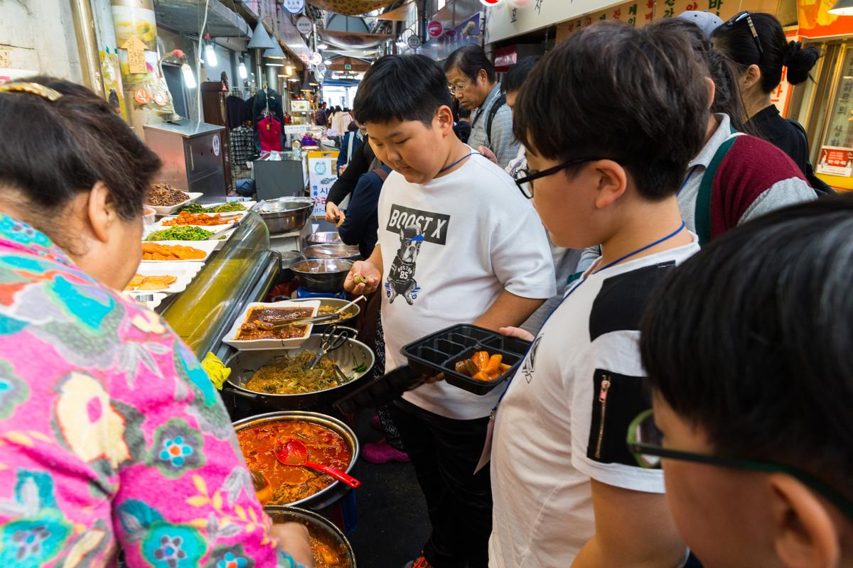 學童校外教學體驗銅錢購買小吃的古早文化。