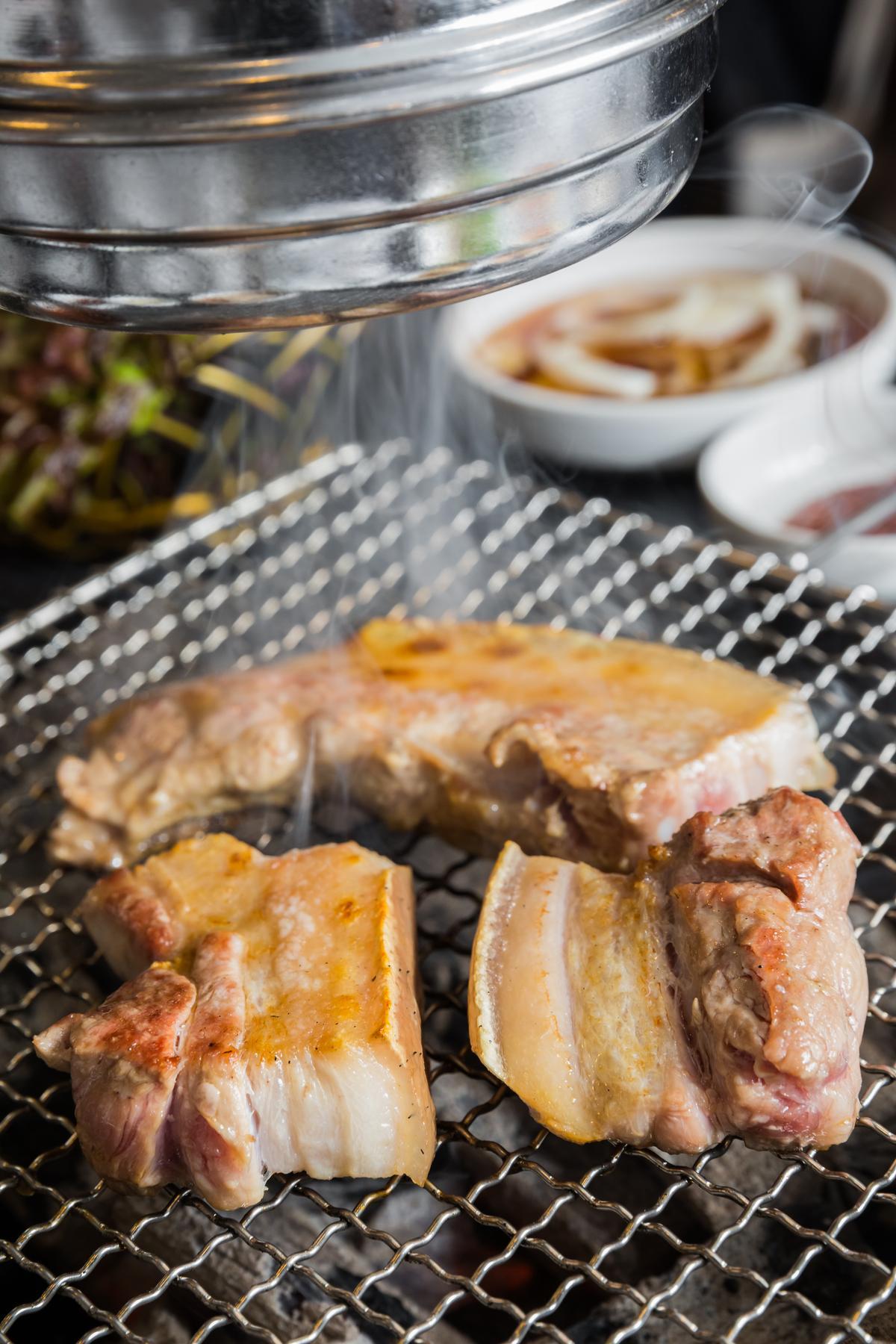 將兩大塊帶皮豬五花放上烤網,油脂與炭火共伴,發出滋滋作響的效果音。