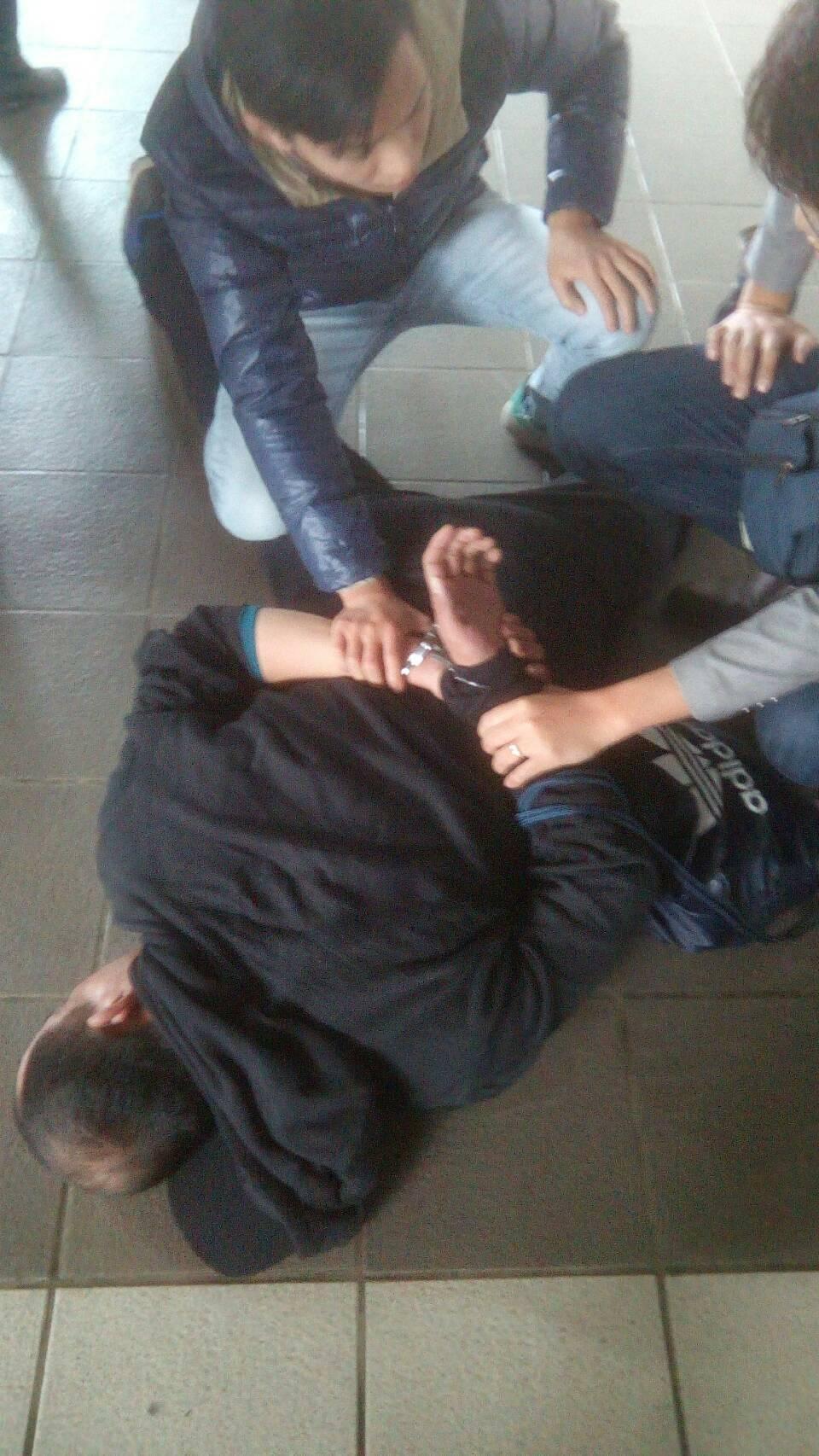 一身黑色愛迪達裝扮的林嫌於台南高鐵站落網並遭壓制在地。(警方提供)