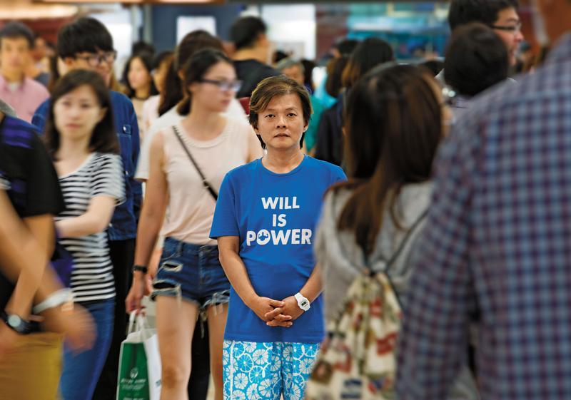 站在人群中,丘愛芝顯得更嬌小,他的生命故事深沉,但堅強的意志給了他面對自我的力量,如同T恤上的標語。