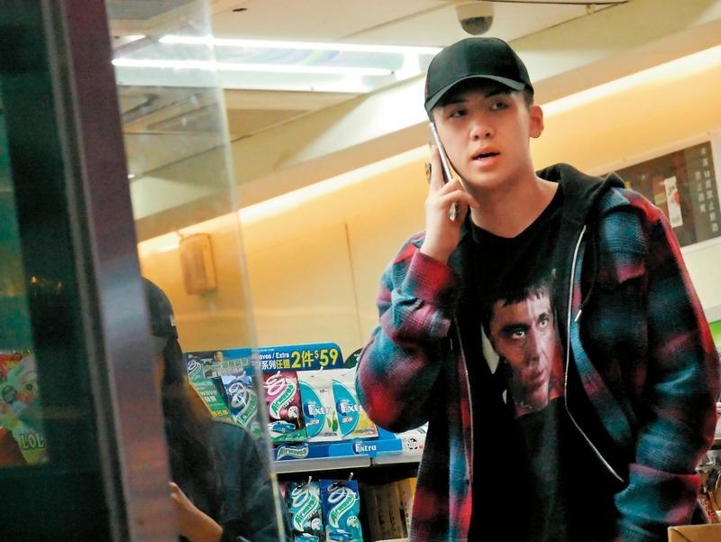 寶弟在超商裡一直忙著講電話,女伴在旁滑手機。